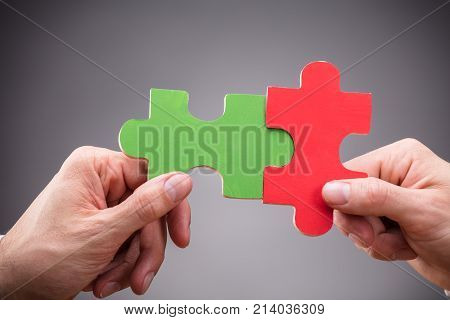 Close-up Of Two People Holding Red And Green Jigsaw Puzzle On Grey Background