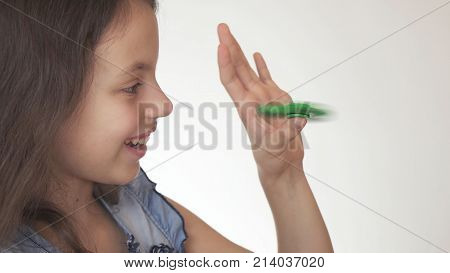 Beautiful cheerful teen girl playing with green fidget spinner on a white background