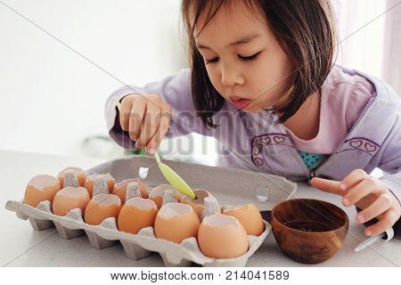Mixed Asian Girl Planting Seeds Into Eggshells, Eco Gardening,  Montessori, Education, Reuse Concept