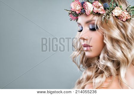 Cute Woman with Pink Roses Flowers and Green Leaves Wreath Blonde Curly Hair and Healthy Skin. Skincare and Haircare Concept