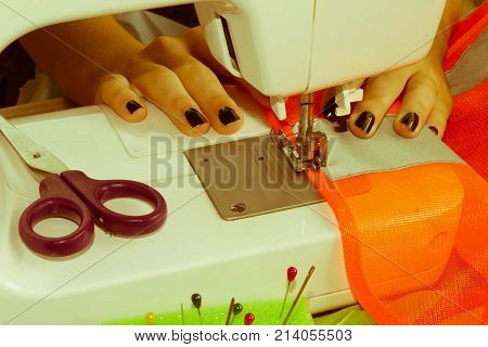 Dressmaker woman working with sewing machine. Sewing Process the sewing machine sew women's hands. sewing machine and female scissors poster