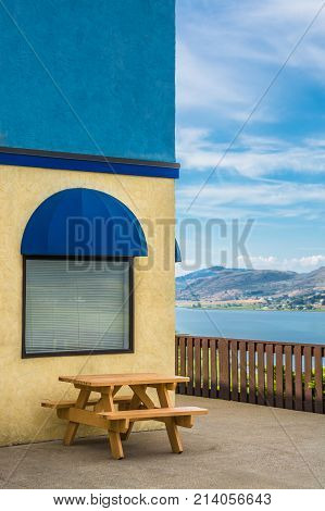 Cafe place with wooden table and view. Table and benches at rest area with mountains and cloudy sky background.