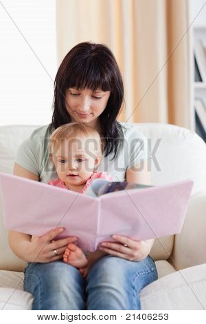 Pretty Woman Holding Her Baby And A Book In Her Arms While Sitting On A Sofa