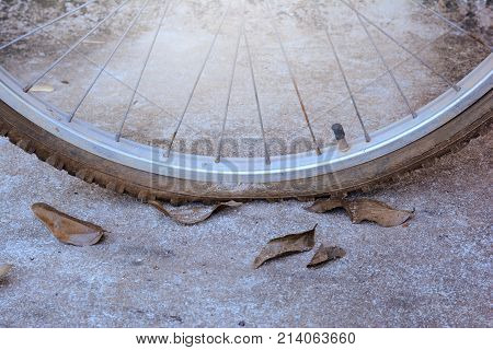 the flat bicycle tire and cracking on rubber skin with dry leaves on concrete street