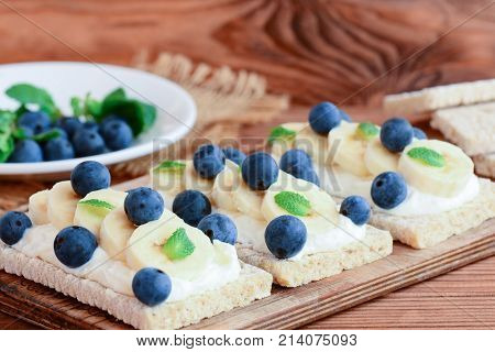 Home crispbread toast with cottage cheese, banana and berries on wooden board. Healthy sandwiches with cottage cheese photo. Closeup