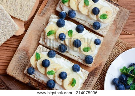 Cottage cheese, bananas and berries sandwiches with crisp bread on wooden board. Great cottage cheese sandwiches recipe. Closeup