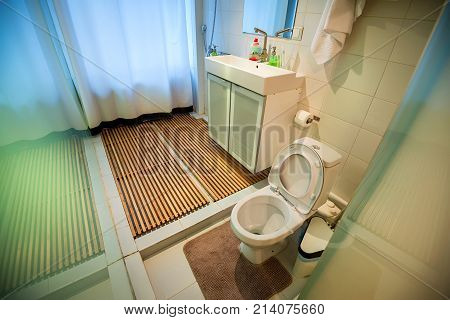 Interior of a modern bathroom with white toilet, shower and wooden boards