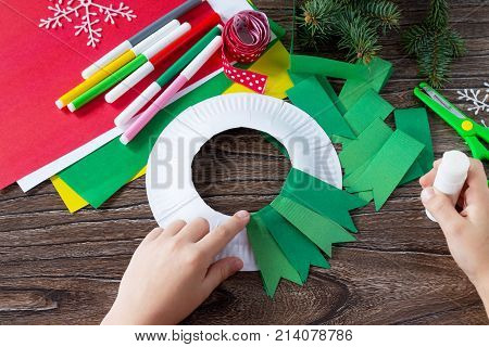 The Child Glues The Details Of The Christmas Wreath With A Candle. Made By Own Hands. Children's Art