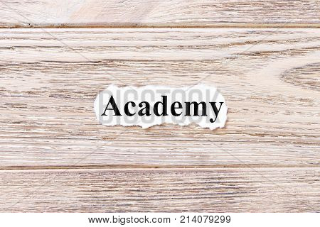 ACADEMY of the word on paper. concept. Words of ACADEMY on a wooden background.