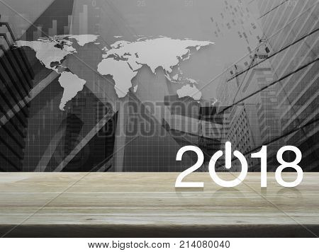 2018 start up business icon on wooden table over world map with financial graph and city tower Happy new year Elements of this image furnished by NASA