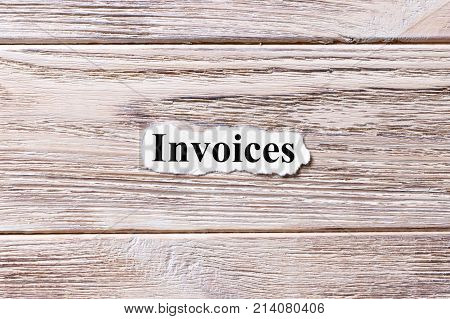 Invoices of the word on paper. concept. Words of Invoices on a wooden background.