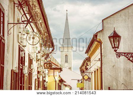 Hrnciarska street with Calvinist church in Kosice Slovak republic. Folk art theme. Religious architecture. Yellow photo filter.