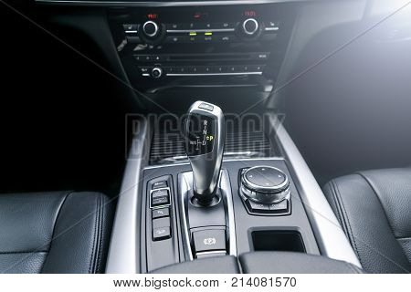 Automatic gear stick (transmission) of a modern car multimedia and navigation control buttons. Car interior details. Transmission shift. Soft lighting