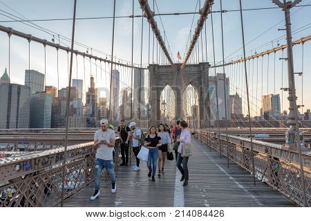 People walk across the Brooklyn bridge at sunset on June 26, 2017 in New York. The Brooklyn Bridge is one of the oldest suspension bridges in the United States.
