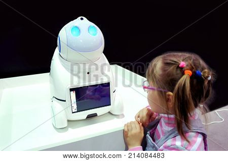 MOSCOW, RUSSIA - NOVEMBER 5, 2017: The girl at the exhibition with the children's robot babysitter UNO.
