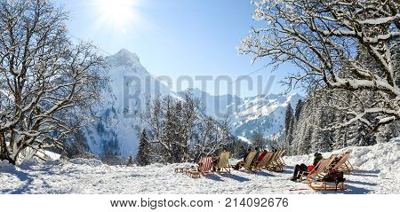 Group of people sitting with deck chairs in sunny winter mountains. Sunbathing in snow. Germany, Bavaria, Allgau, Schwarzenberghuette.