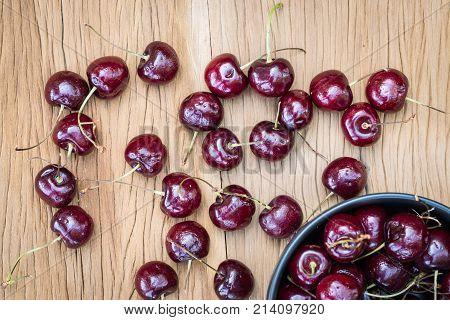 Cherry With Black Bowl On Wooden Table Taken In Top View