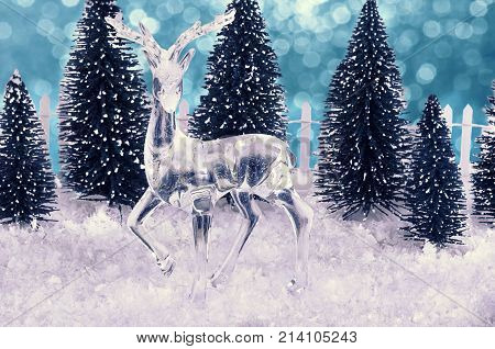 Glass deer decoration on snowflakes. Bokeh lights in background.