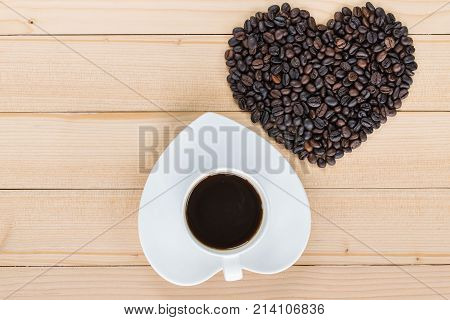 Heart Shaped Coffee Cup And Coffee Beans On A Wooden Background