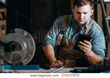 Self-employed machine constructor calculating costs while working at manufacturing plant poster