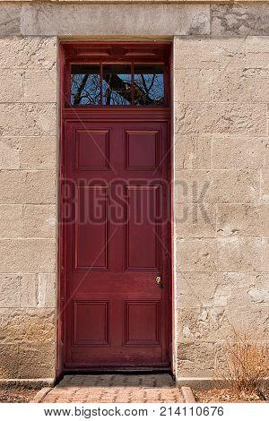 Dark red wooden entrance door. Front view.