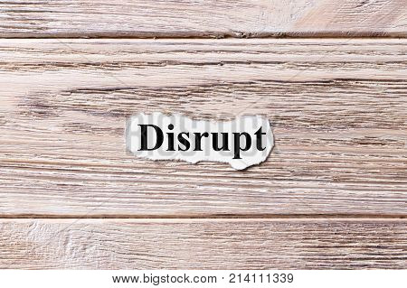 DISRUPT of the word on paper. concept. Words of DISRUPT on a wooden background.