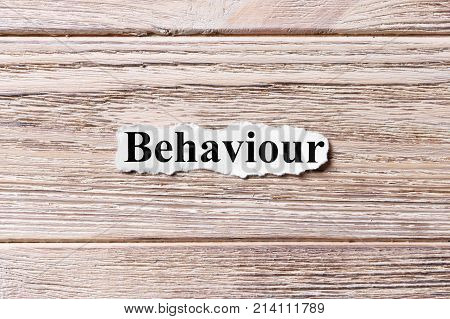 behaviour word on paper. concept. Word behaviour on a wooden background.