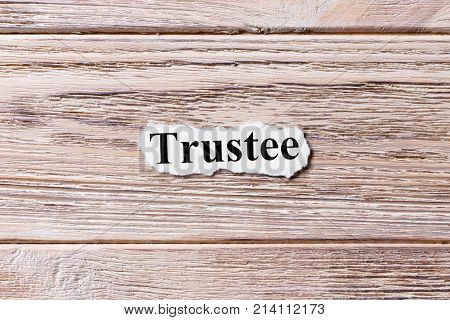 Trustee of the word on paper. concept. Words of Trustee on a wooden background.
