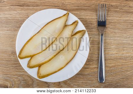 Slices Of Smoked Halibut In Plate And Fork On Table