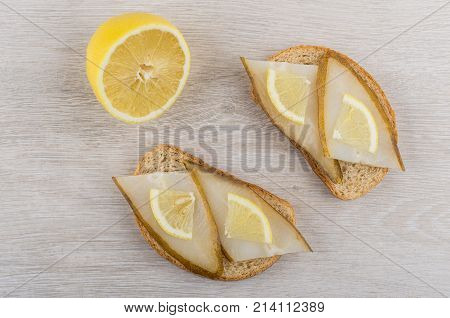 Half Of Lemon And Sandwiches With Smoked Halibut On Table