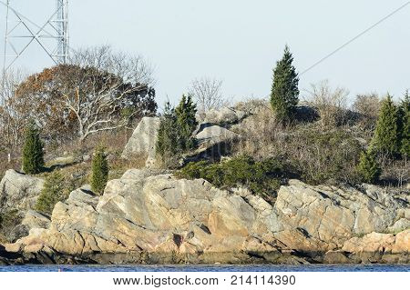 Granite hillside and scruffy trees on Palmer's Island at entrance to New Bedford Massachusetts inner harbor