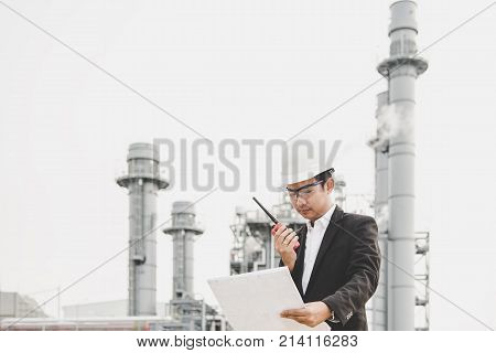 Engineer man holding white helmet and blueprint with radio for workers security control at power plant energy industry. Engineer Concept