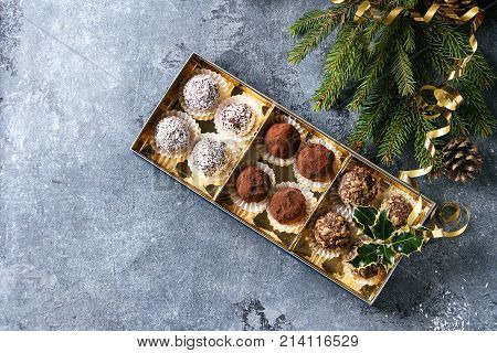 Variety of homemade dark chocolate truffles with cocoa powder, coconut, walnuts as Christmas gift in golden box with fir tree, Christmas decorations above over blue background. Top view, copy space.