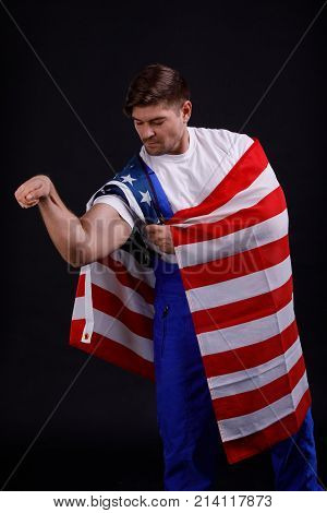 Worker inflated showing a hand-pumped hand with an American flag on his shoulders against a black background