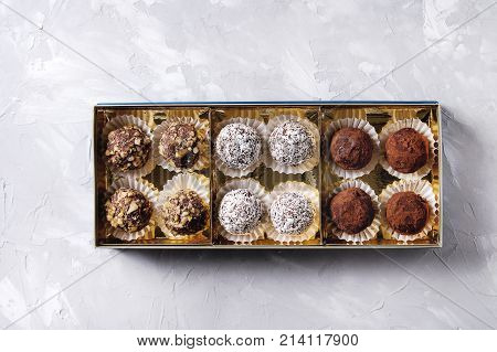 Variety of homemade dark chocolate truffles with cocoa powder, coconut, walnuts in golden gift box over gray texture background