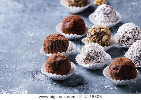Variety of homemade dark chocolate truffles with cocoa powder, coconut, walnuts over blue texture background.