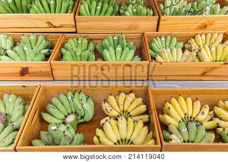 Banana with price tag in wooden container at retail market