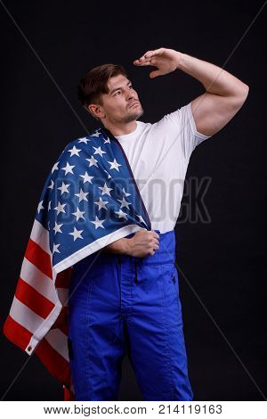 Worker inflated in uniform holding an American flag and looking afar on his shoulder against a black background