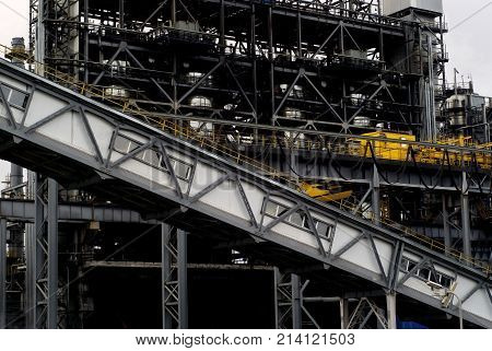 industrial background: a fragment of some industrial structure with a weave of steel beam structures and inclined covered belt conveyor