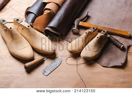 Leather in rolls cobbler tools and shoe lasts in a workshop. Leather craft tools.