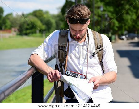 Discovering new places concept. Man with backpack and sunglasses holding map and looking at it on city street background.