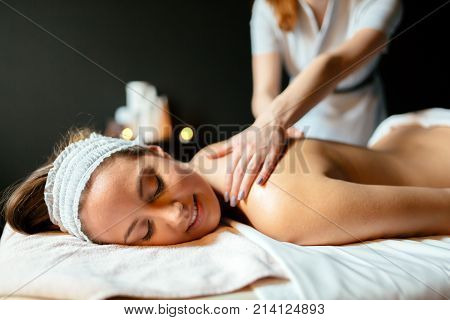 Massage therapist massaging beautiful brunette in a spa