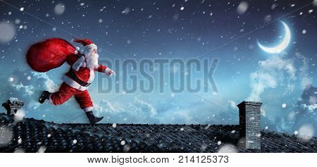 Santa Claus Running On The Rooftops With Sack