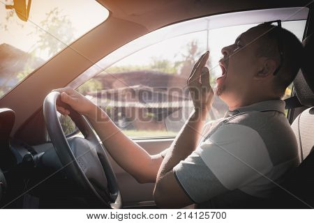 Sleepy yawning man driving car in traffic after long hour drive. Man falling asleep in car.