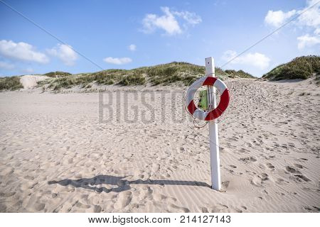 Lifesaver hanging on a post on an Scandinavian beach in red and white colors in the summer