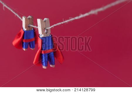 Toy clothespin peg superheroes on rope clothesline. Big small super team characters red background. soft focus. macro view, shallow depth of field.