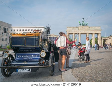 BERLIN GERMANY - AUGUST 25 2017; Neo-classical architectureof Barndenburg Gate in background selfie taking tourist by replica carriage on street with sign