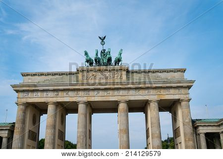 BERLIN GERMANY - AUGUST 25 2017; Neo-classical architecture and bronze statue four hourses pulling chariot on top of the Brandenburg Gate