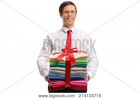 Formally dressed man holding a stack of ironed and packed clothes wrapped with a red ribbon as a gift isolated on white background