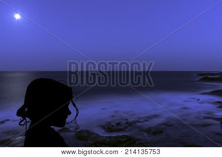 Silhouette of a young girl with the moon over the ocean in Los Cocoteros, Lanzarote, Spain